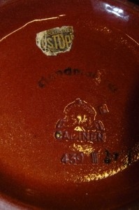 Wycisk ze stylizowanym znakiem korony wraz z umieszczonym  poniżej napisem CADINEN, numerem formy i oznakowaniem wielkości oraz nalepką domu towarowego.