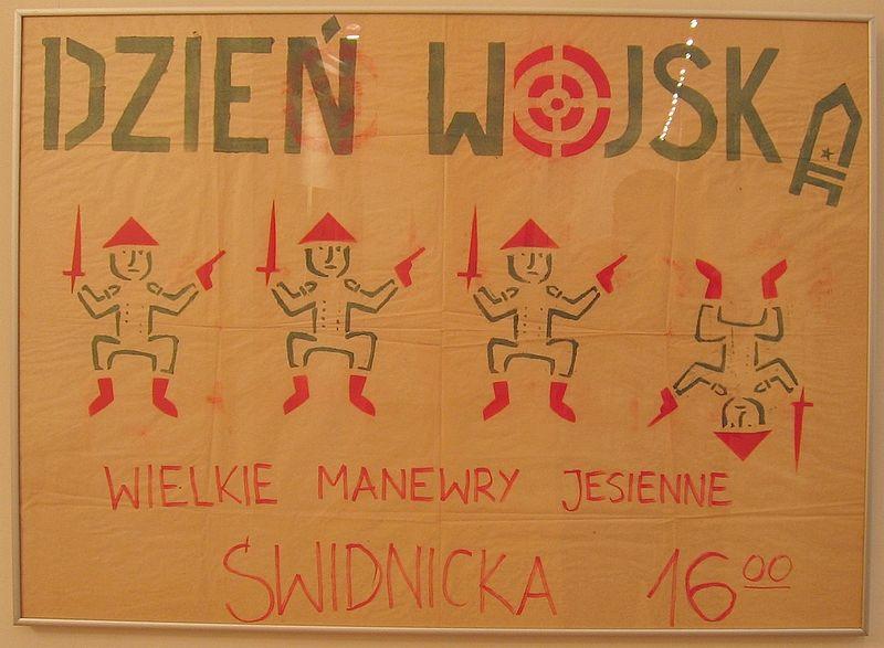 """Plakat """"Pomarańczowej Alternatywy"""" zapowiadający happening z okazji """"Dnia Wojska"""" z 12 października 1987 roku przedstawiający uzbrojone krasnoludki. źródło: Wikipedia"""